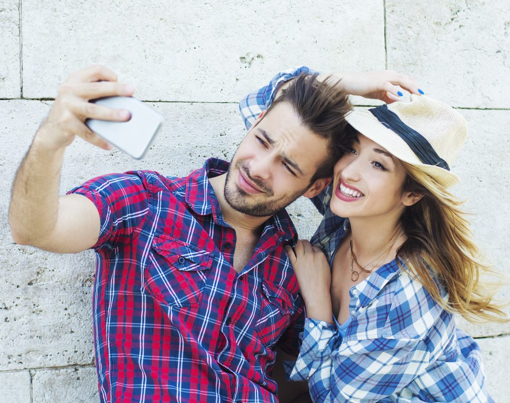 Young couple making selfie in front of wall